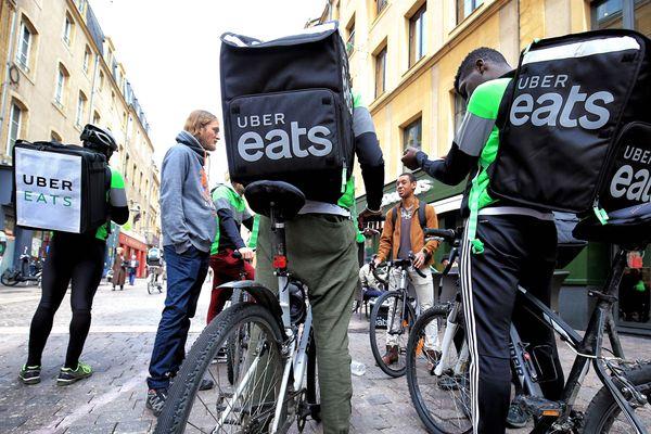 Des coursiers à vélo travaillant pour l'entreprise Uber Eats.