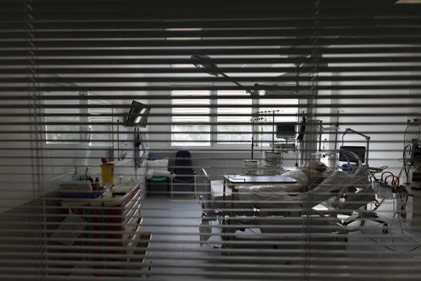 Un patient dans un lit d'hôpital, caché par des stores - Photo d'illustration