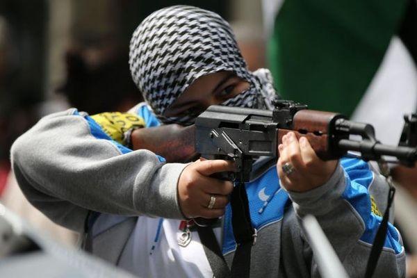 Une manifestante tient dans ses mains une Kalachnikov ou une copie de ce célèbre modèle de fusil d'assaut, à l'occasion d'une manifestation à Paris, samedi 9 août 2014.