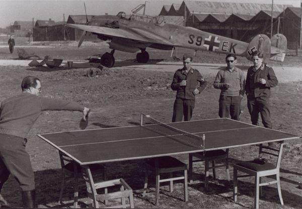 Des membres de la Luftwaffe jouant au tennis de table devant un chasseur-bombardier Messerschmitt Bf110 (ou Me 110) sur un aérodrome lillois en 1940.