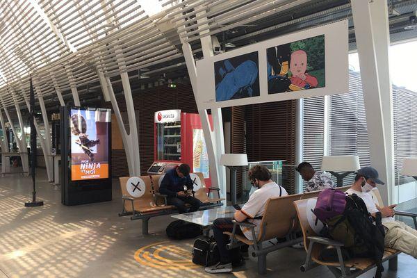 En gare de Montpellier, les annonces rappellent le port du masque obligatoire et les sièges sont limités dans les espaces d'attente.