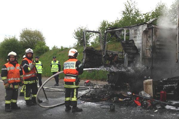 Des pompiers de plusieurs localités de Corrèze éteignant l'incendie d'un semi-remorque au bord de l'autoroute A 20 ( Saint-Pardoux l'Ortigier, 19) lundi 13 mai