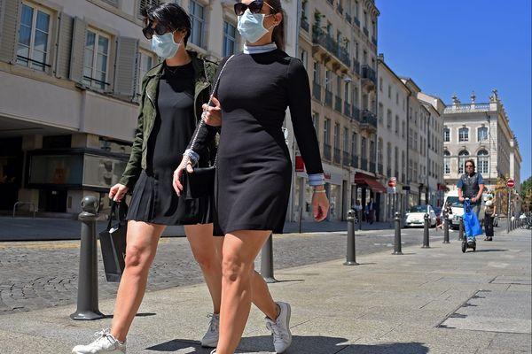 Deux jeunes filles se promènent en ville avec des masques