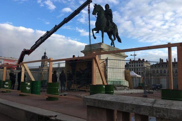 Lyon : la statue de Louis XIV, place Bellecour, va bientôt quitter son piédestal pour être restaurée. Les statues de bronze des frères Coustou ont déjà été placées dans des caisses de bois en fin de semaine dernière.
