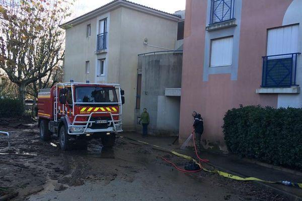 Des pompiers nettoient la boue devant la résidence Les platanes à Mandelieu, le 2 décembre 2019