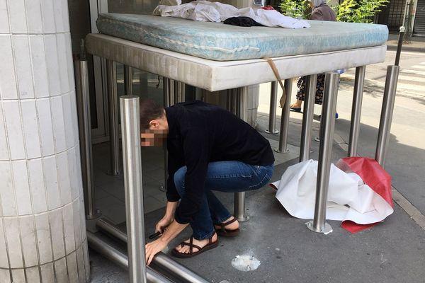 Un homme dévisse les poteaux anti-SDF devant la Caisse d'Epargne à l'angle de la rue d'Alésia et de la rue rue Hippolyte Maindron.