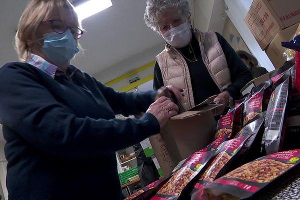Deux bénévoles de la Papothèque préparent des colis alimentaires le 29 janvier 2021 à Grenoble.