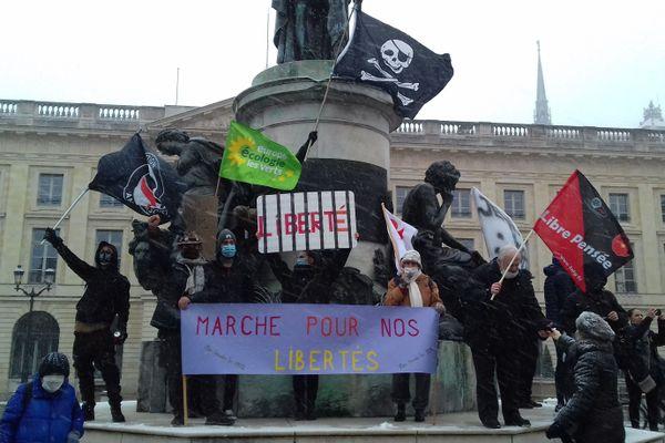 Des drapeaux revendicatifs agités sur le socle de la statue de Louis XV, place Royale.