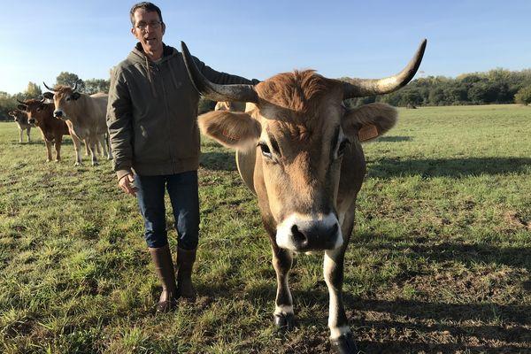Benoît Rolland  avec Griotte, l'une de ses vaches qui paissent sur des terres confiées par Nantes Métropole.