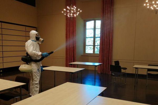 Un agent de nettoyage est en pleine opération de désinfection dans une salle municipale de Sézanne. Ici aura bientôt lieu une campagne de don du sang. Entreprise CAT 3D.