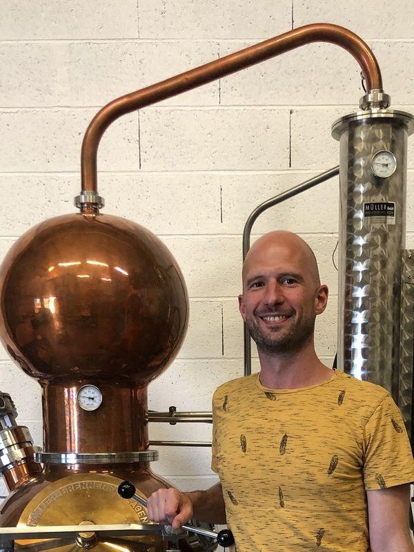 Nicolas, l'un des quatre strasbourgeois à l'origine de la micro-distillerie, devant l'alambic de l'atelier.