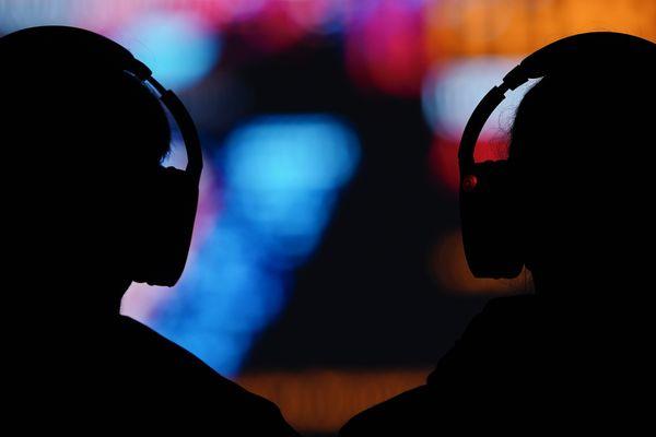 Deux silhouettes portant des casques audio sur la tête, le 29 août 2020, lors d'un festival allemand.