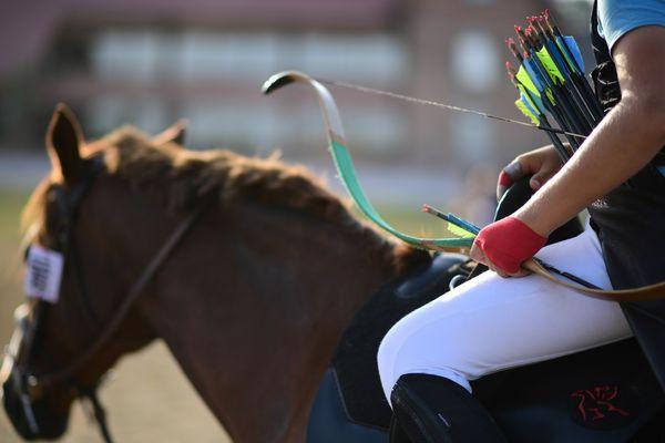 Une jeune femme tient son arc et ses flèches, assise sur son cheval, à Lamotte-Beuvron.