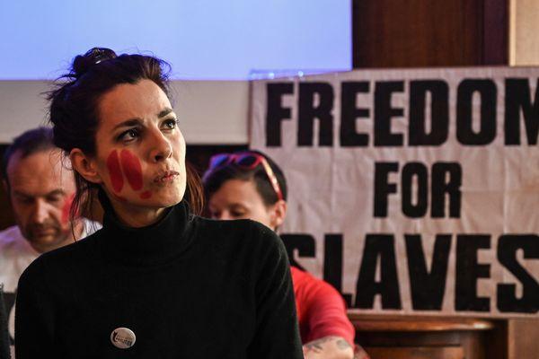 """L'une des militantes condamnées, lors d'une conférence de presse en juin 2019, avec une pancarte """"Liberté pour les esclaves""""."""