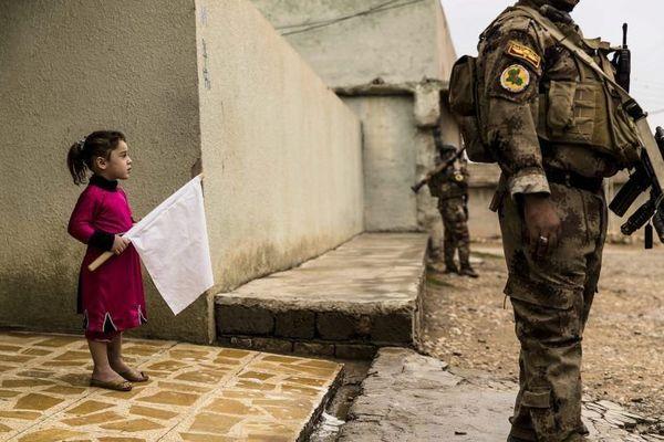 2 novembre 2016, Gogjali, Mossoul-Est. Pendant que les hommes du premier bataillon de l'ISOF 1 du colonel Mohaned sécurisent les ruelles du quartier, une petite fille sort de chez elle à la rencontre des soldats, un drapeau blanc à la main