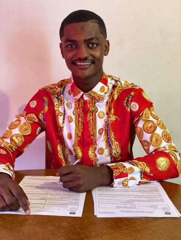Ismaël Boura, tout sourire au moment de signer son premier contrat pro.