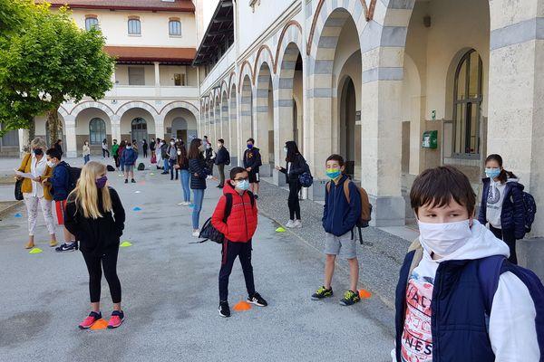 Les élèves masqués attendent sur un plot que leur professeur vienne les chercher