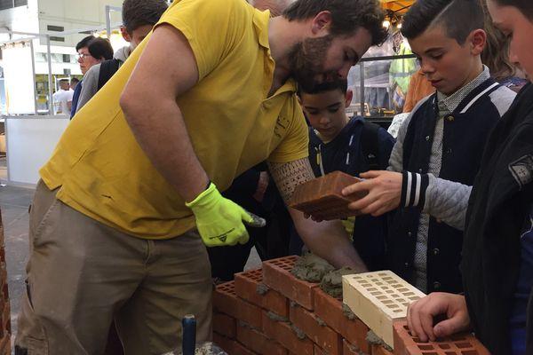 Des jeunes visiteurs bâtissent un mur aux Olympiades des Métiers.