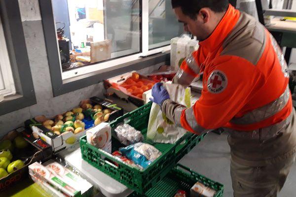 un bénévole de La Croix-Rouge Française prépare des panier-types pour ravitailler les personnes isolées.
