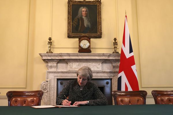 La Première ministre Theresa May signant la lettre officielle demandant la sortie du Royaume-Uni de l'Union Européenne.