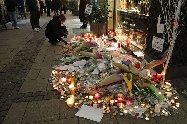 Des personnes se recueillent devant un parterre de fleurs et de bougies en hommages aux victimes, rue des Orfèvres à Strasbourg après l'attentat du 11 décembre 2018