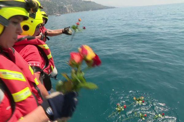 Les secouristes jettent des fleurs à la mer en hommage à leurs collègues disparus.