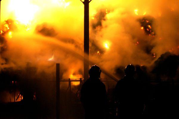 Les sapeurs pompiers en intervention à l'aide d'une lance à eau dans un hangar agricole en flammes (2007)