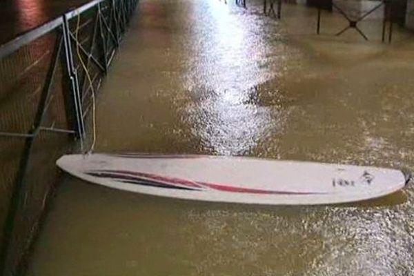 Un cafetier profite de la montée des hauts pour surfer, en attendant de pouvoir estimer les dégâts causés par l'eau.