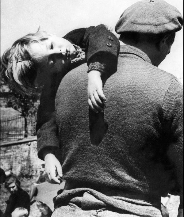 Un père emporte son enfant, fuyant les bombardements et l'arrivée des troupes allemandes - figures symboliques de l'exode dans le nord de la France, en mai 1940, durant la seconde guerre mondiale.