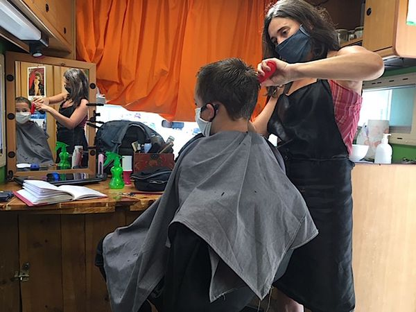 Sonia coiffe César dans son salon itinérant aménagé dans un camping-car à Fourquevaux