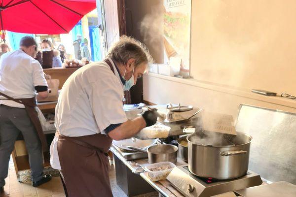 C'est sous un porche que les deux cuisiniers préparent leur cuisine de rue.
