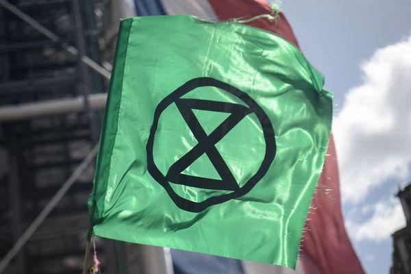 Un militant d'Extinction Rebellion brandit un drapeau aux couleurs du mouvement à Paris, lors d'une manifestation en avril 2019 (illustration).