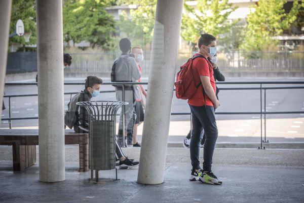 Des collégiens portant le masque devant leur établissement (Illustration)