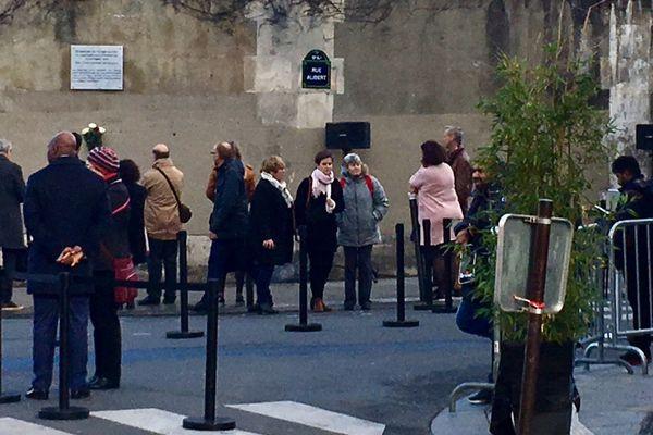 Élisabeth Boissinot, de dos en rose, devant la plaque commémorative en hommage aux victimes des attentats du 13 novembre 2015.
