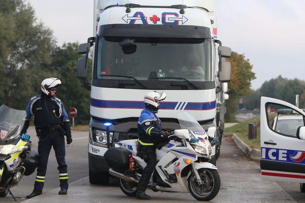 Des CRS intervenant auprès d'un camion à côté d'une autoroute. (image d'illustration)