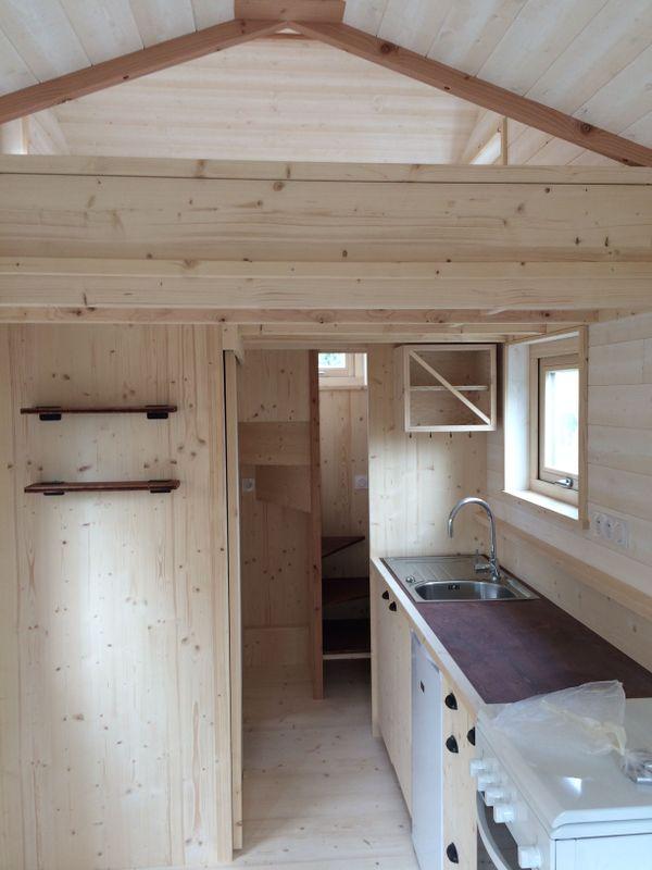 L'intérieur, non fini, d'un modèle de mini-maison, au fond, la salle d'eau et en mezzanine, la chambre