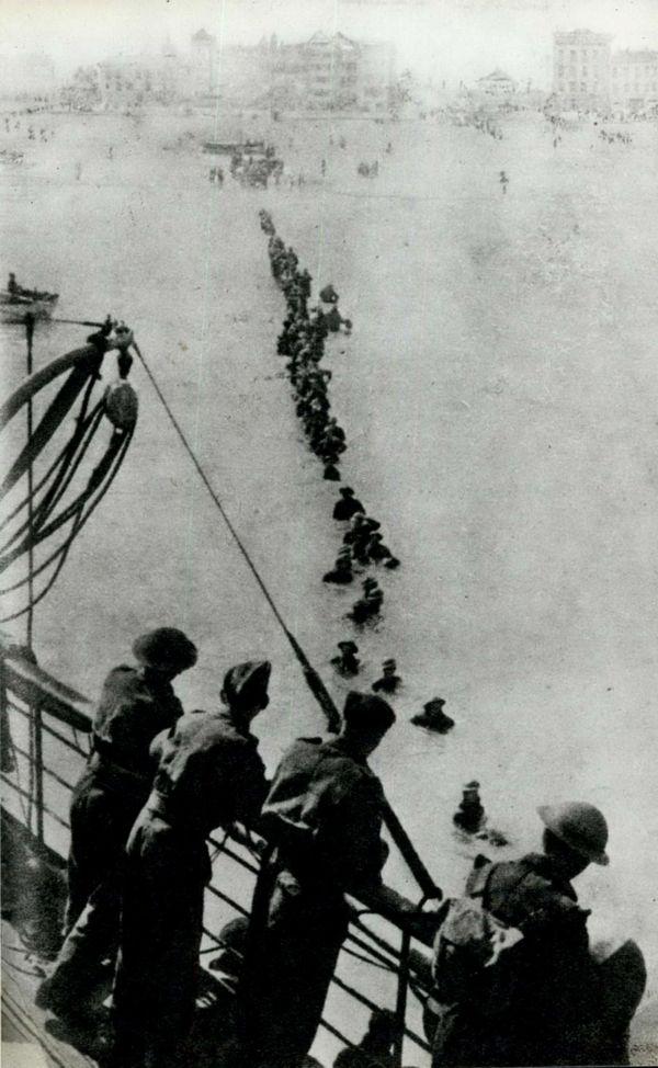 Des soldats britanniques en file indienne, dans l'eau, pour accéder à un navire, lors de l'Opération Dynamo.