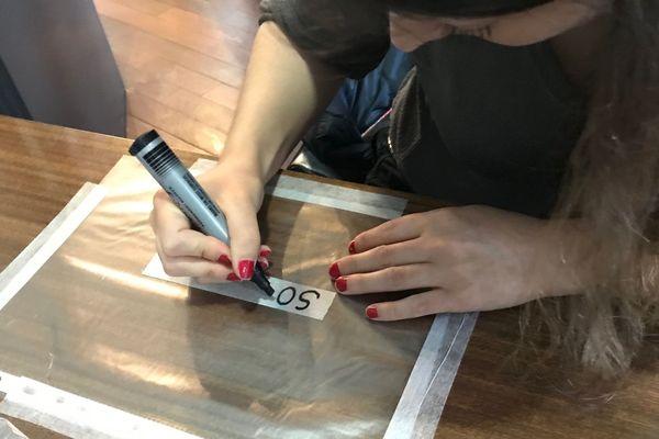 Atelier masque : chacun inscrit le/les mot(s) de son choix sur une bande collante, à appliquer entre les plis du masque