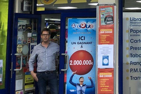 """François Groux, gérant de la """"Presse du Parc"""" à roubaix pose à côté de l'affaiche """"Ici un gagnant à 2 000 000 €"""