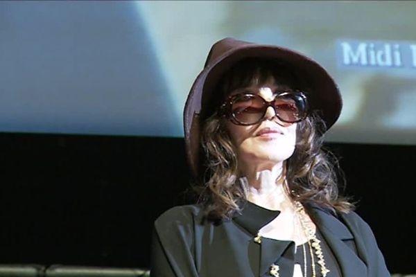 l'actrice Isabelle Adjani, capeline vissée sur la tête et lunettes de soleil au bout du nez, sur la scène du Corum, lors du Cinemed 2016.