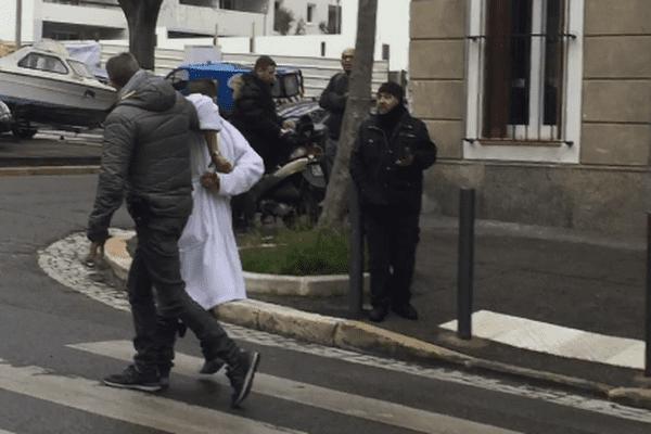 Le forcené, ici en peignoir blanc, lors de son interpellation, boulevard Oddo à Marseille.