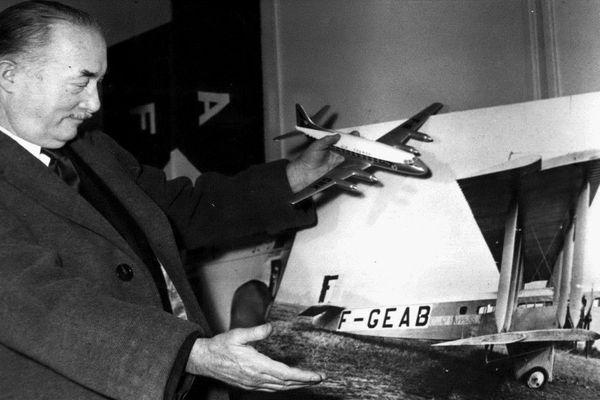 Lucien Bossoutrot en 1949 devant la photo de l'appareil à bord duquel il effectua le premier vol commercial de l'histoire entre Paris et Londres le 8 février 1919