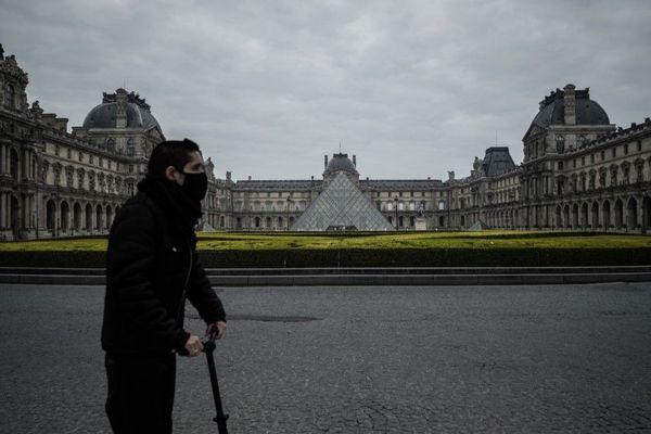Un homme équipé d'un masque au guidon d'une trottinette, mercredi 18 mars à deux pas du Louvre (illustration).