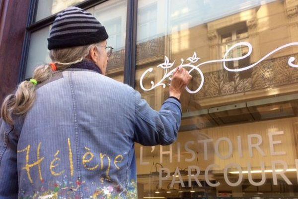 Hélène Geyre peint la vitrine de l'office du tourisme à Carcassonne
