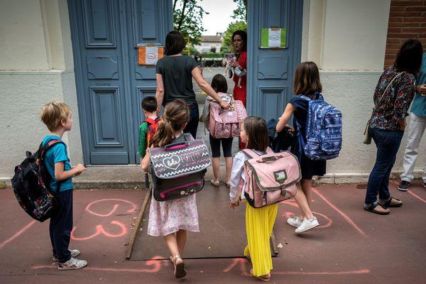 Des parents et leurs enfants arrivent devant une école élémentaire pour la reprise. (Illustration)