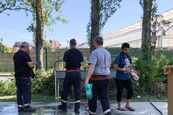 Une entreprise installe des sanitaires près d'un gymnase de Grande-Synthe, autour duquel vivent des centaines de personnes migrantes.