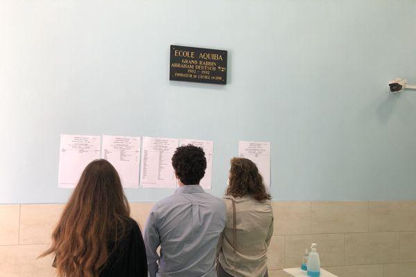 Après les avoir vu en ligne, trois étudiants de l'école Aquiba de Strasbourg redécouvrent leurs résultats du baccalauréat.