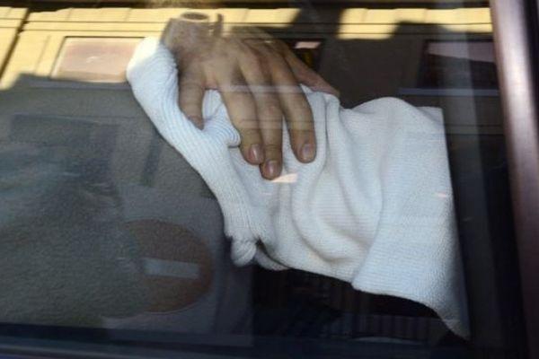 Nîmes - le meurtrier présumé de la joggeuse de Courbessac, le visage caché, dans une voiture de police au palais de justice - 30 janvier 2013.
