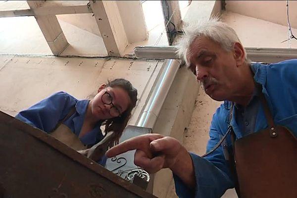 Une jeune fille apprend le maniement des outils avec un forgeron à la retraite