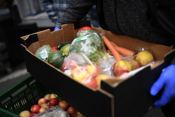 Un bénévole portant une cagette de légumes pour les personnes en situation de précarité. (Illustration)